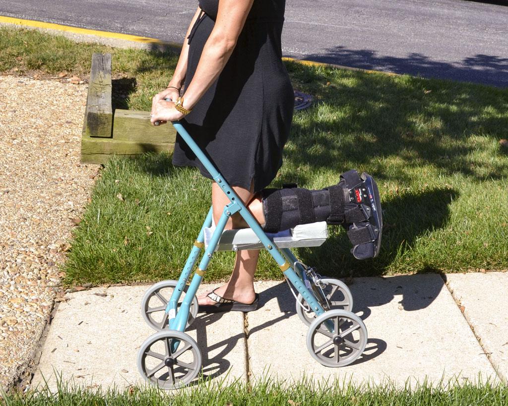 A woman using Standard knee walker